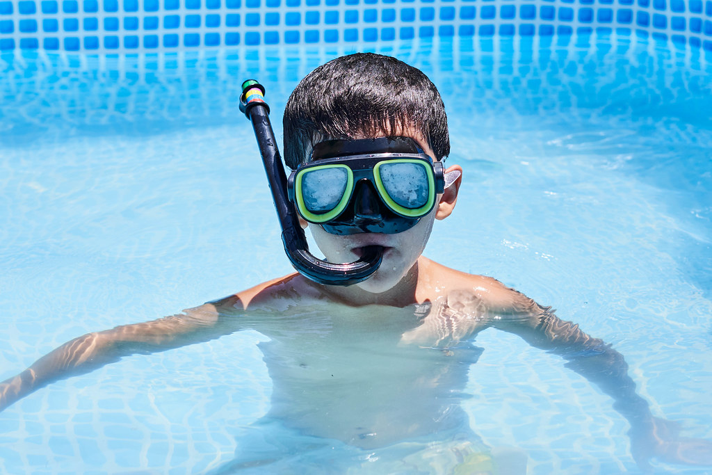 A kid boy of school age wearing mask and snorkel while diving in the pool during summer vacations