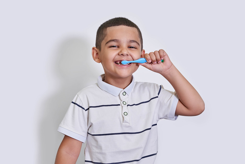 A little mixed-race boy brushing his teeth