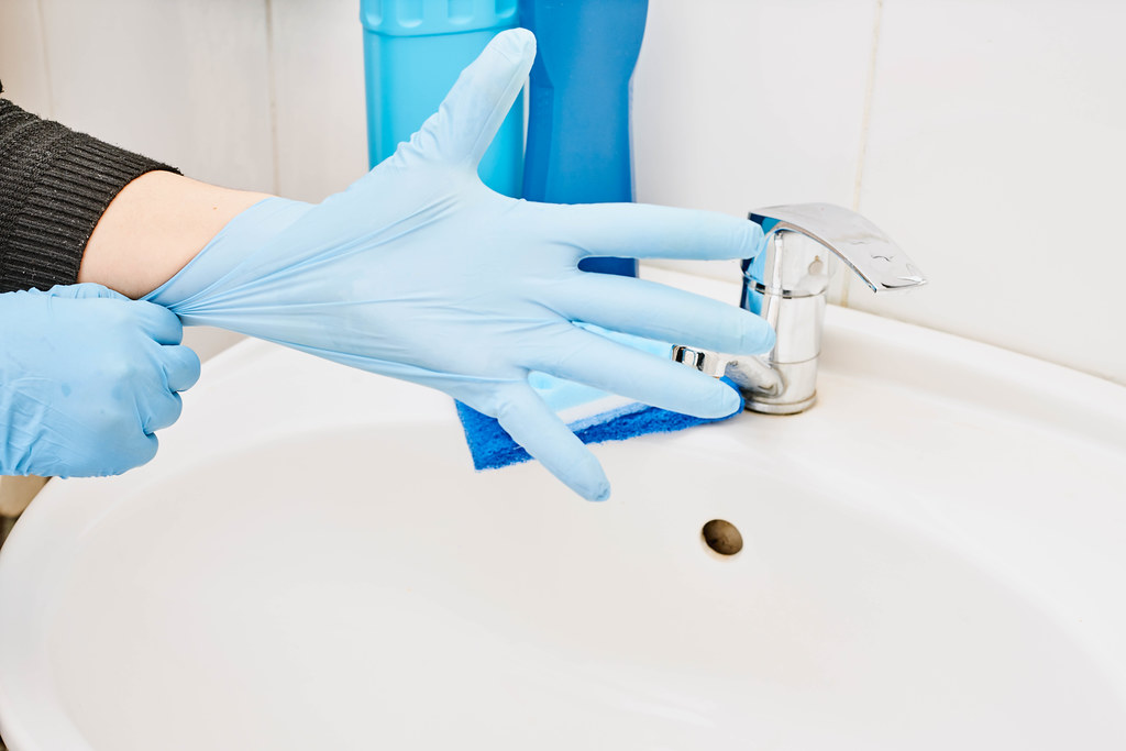 A maid wearing blue rubber gloves and starting to clean the bathroom