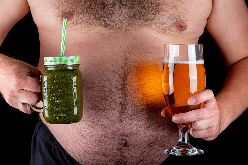 A man holds a glass of beer and a jar of green smoothies. Concept of choice