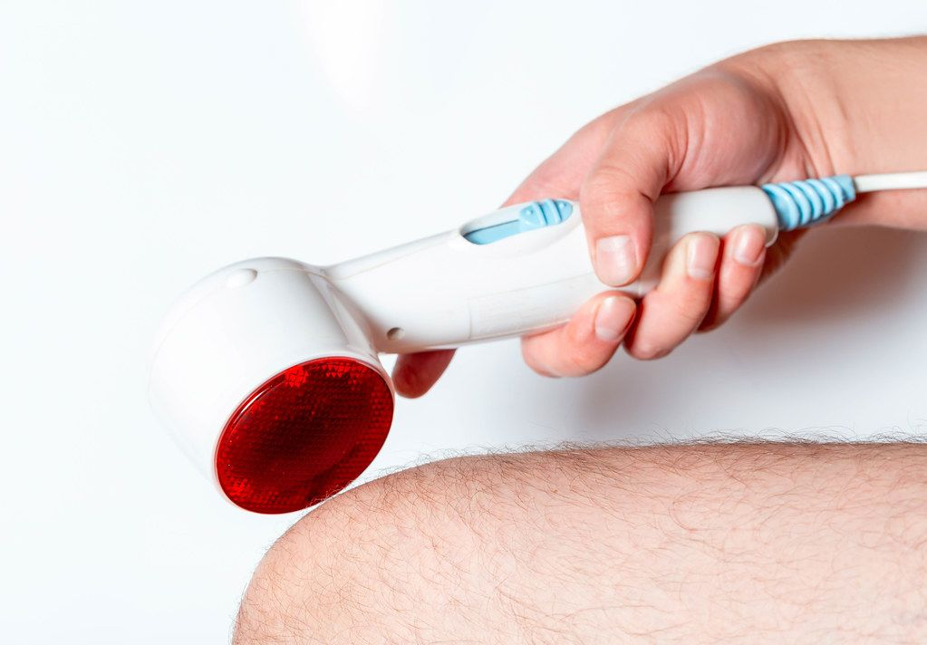 A man holds a heating and massage apparatus near his knee