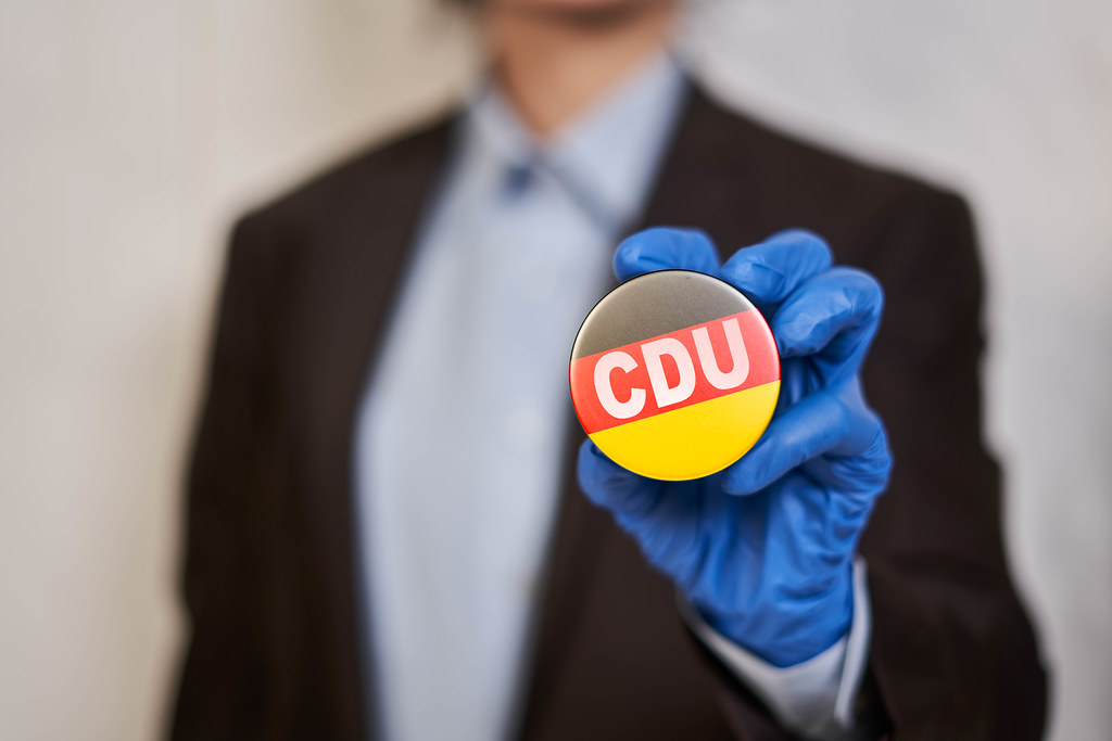 A man in medical gloves holding a vote badge with Christian Democratic Union of Germany symbol