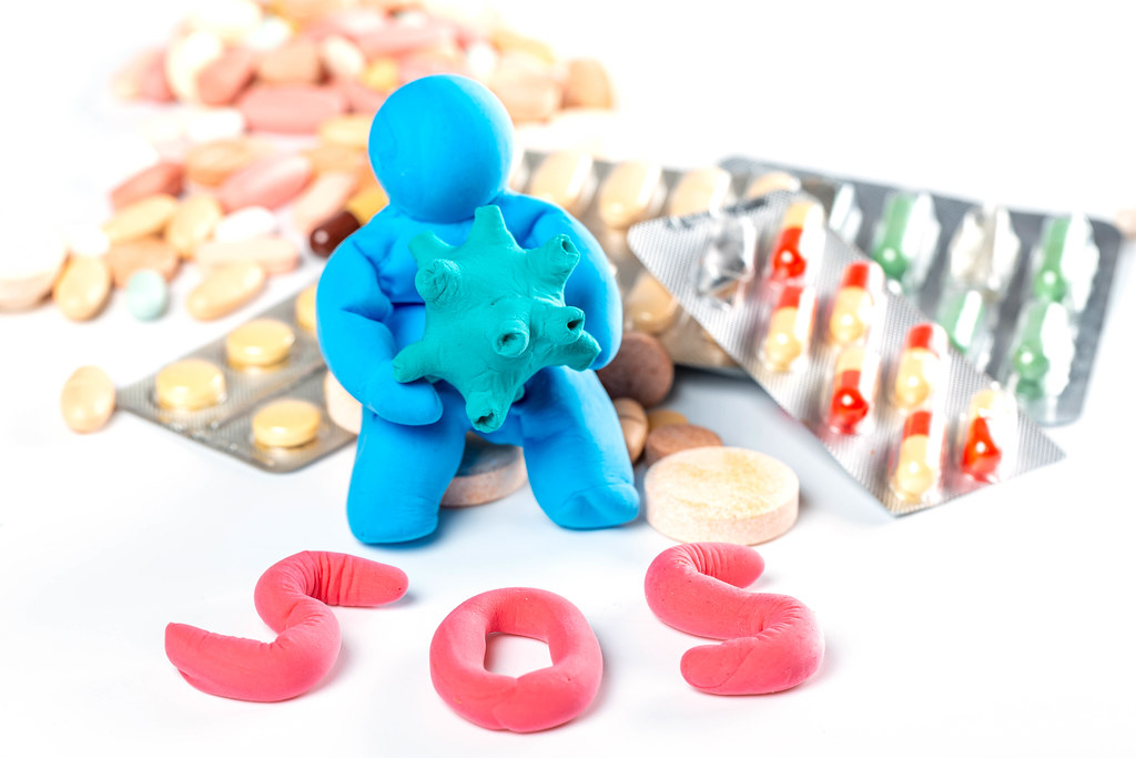 A man made of plasticine with a model of a virus in his hands and a lot of different pills, sign sos