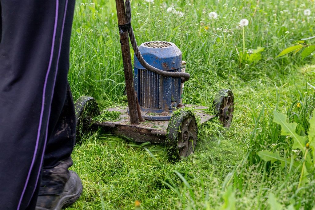 A man mows grass with an old electric lawn mower