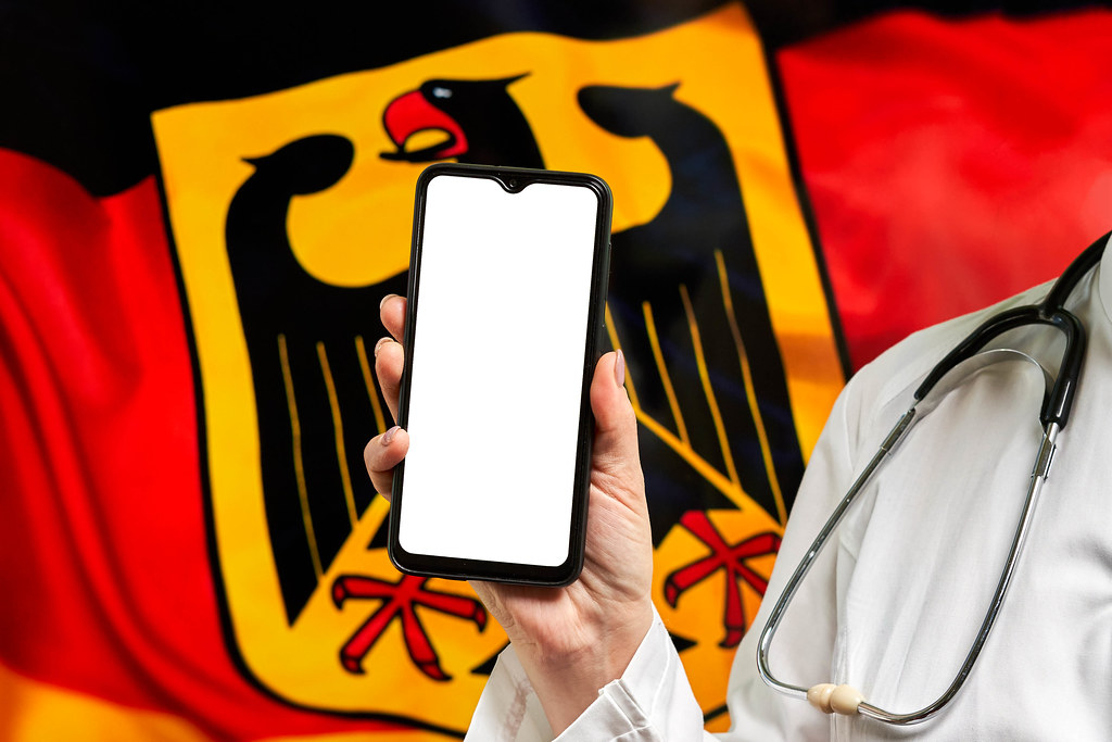 A nurse holding cell phone with empty screen over German flag
