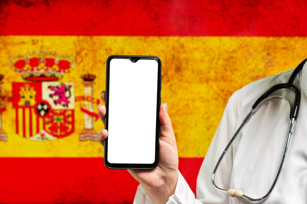 A nurse holding cell phone with empty screen over Spanish flag