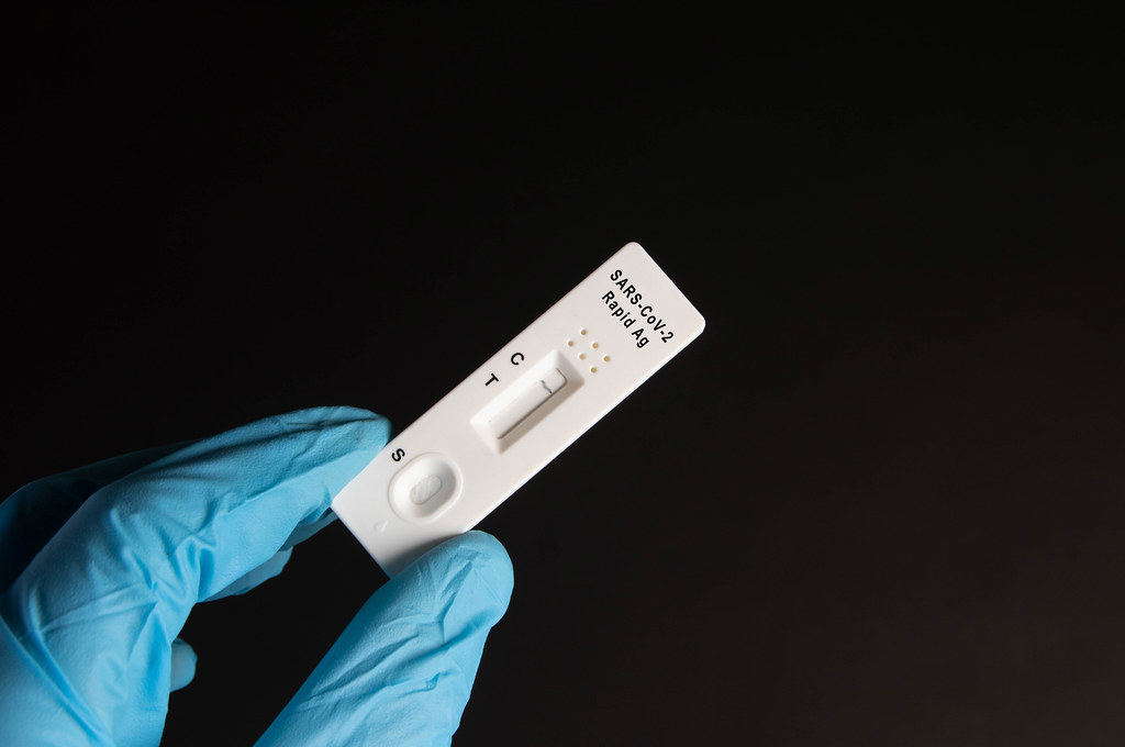 A nurse wearing latex gloves holds a covid-19 antigen test on black background