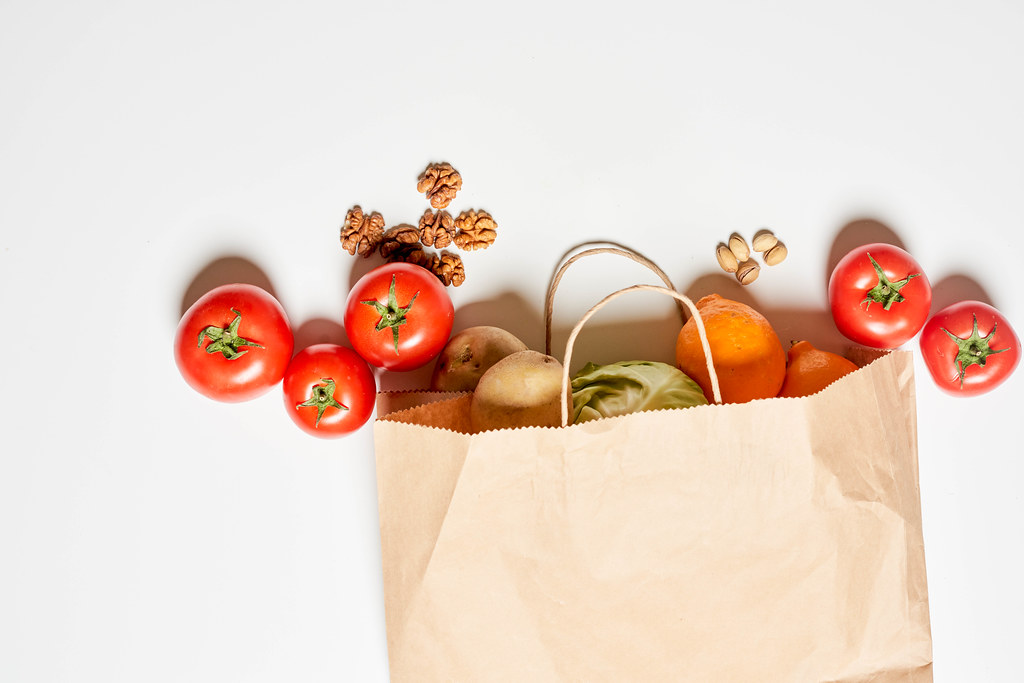 A paper shopping bag full of various organic vegetables and fruits on white background