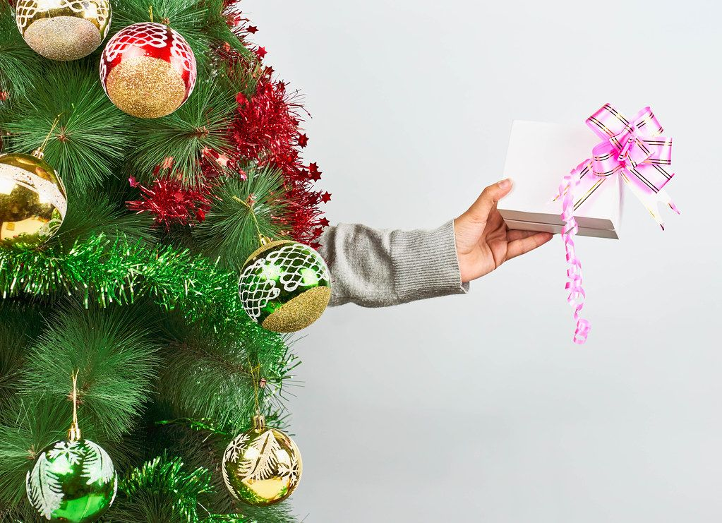 A person holding a cute Xmas present with a pink ribbon