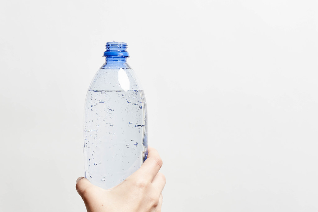 A person holds a bottle of sparkling water