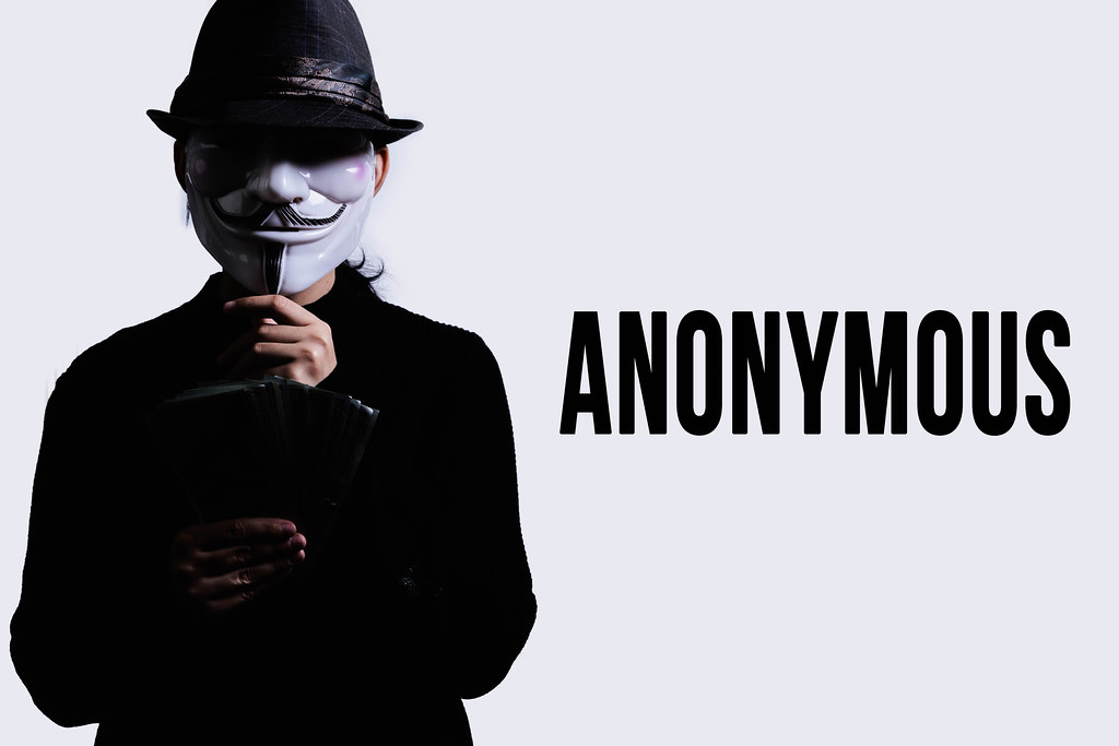 A person in an anonymous mask holding a pile of money. Concept of anonymous donation, hack or robbery