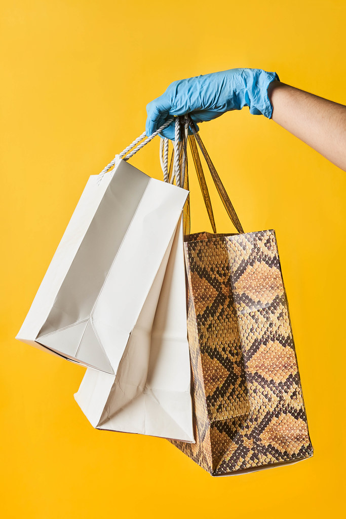 A person in medical gloves holding shopping bags