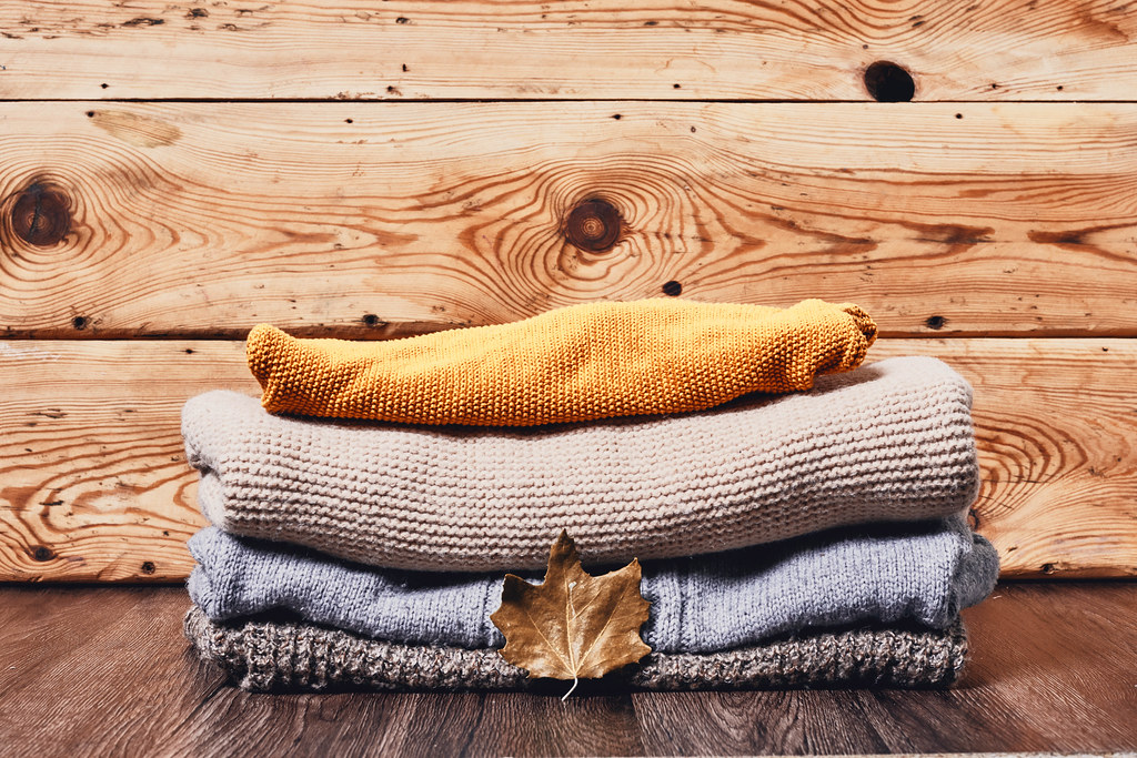 A pile of pullovers on wooden desk