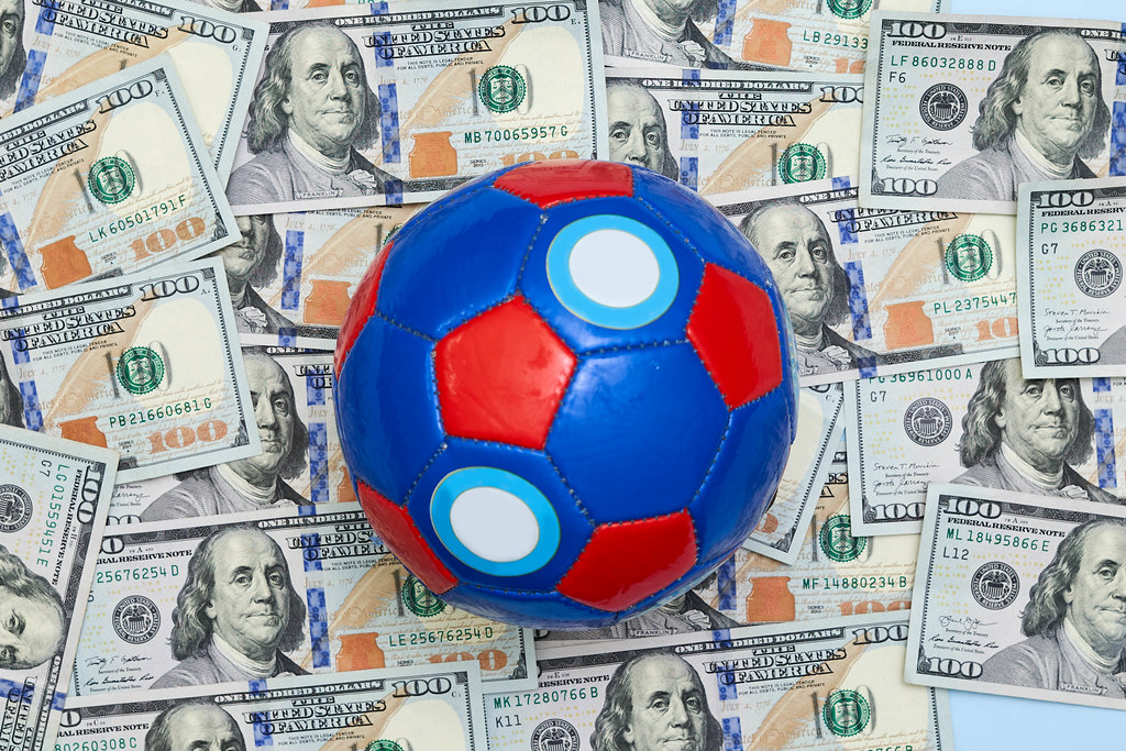A pile of US dollar banknotes and a football ball on it