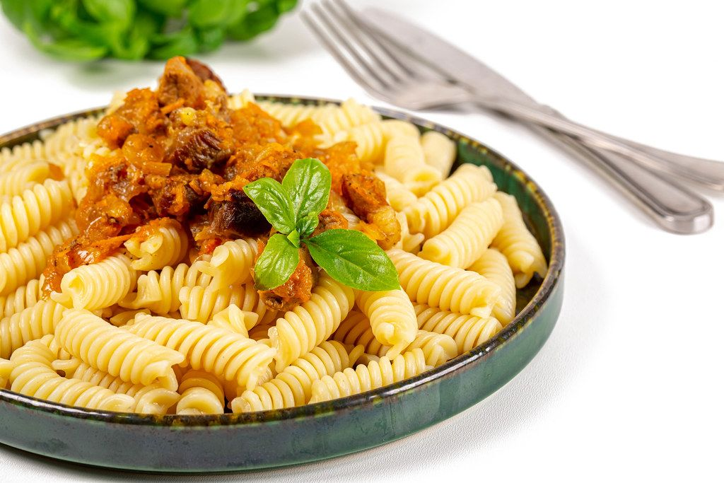 A plate of pasta with gravy and fresh basil leaves
