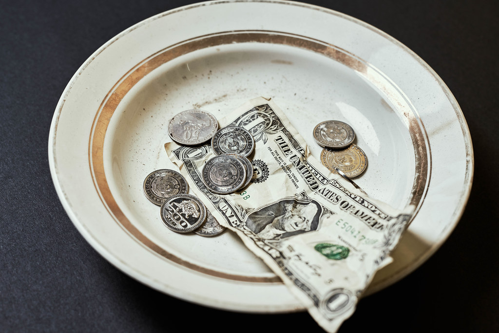 A plate with donated coins and money