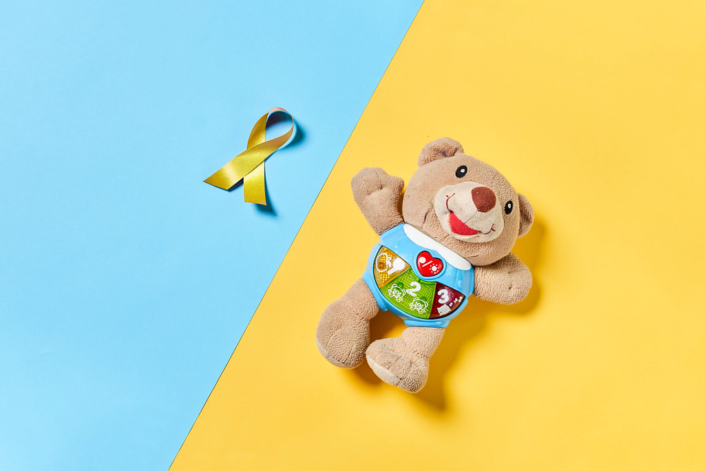 A plush bear toy and yellow gold ribbon, a symbol of childhood cancer awareness