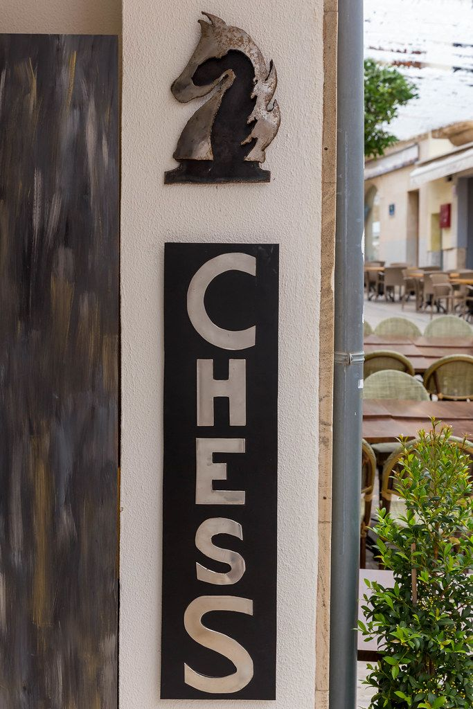 """A """"Chess"""" sign and the symbol of a horse on a building in Alcudía, Majorca"""