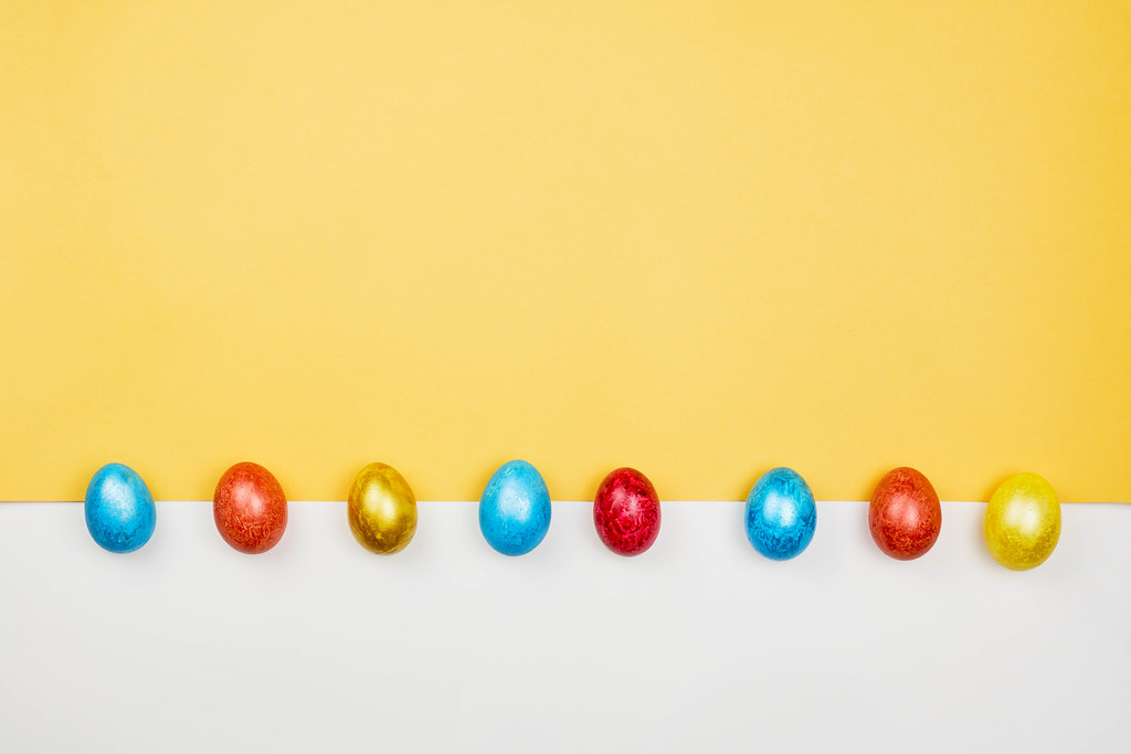 A row of colored Easter eggs on yellow and white background