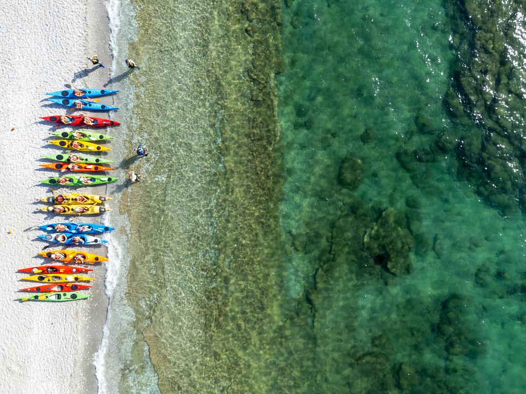 A row of kayaks in various colours on Milia Beach, Skopelos. Bird