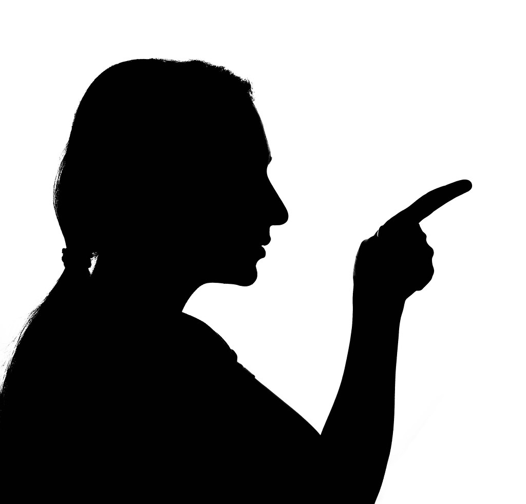 A sad woman silhouette pointing with the finger
