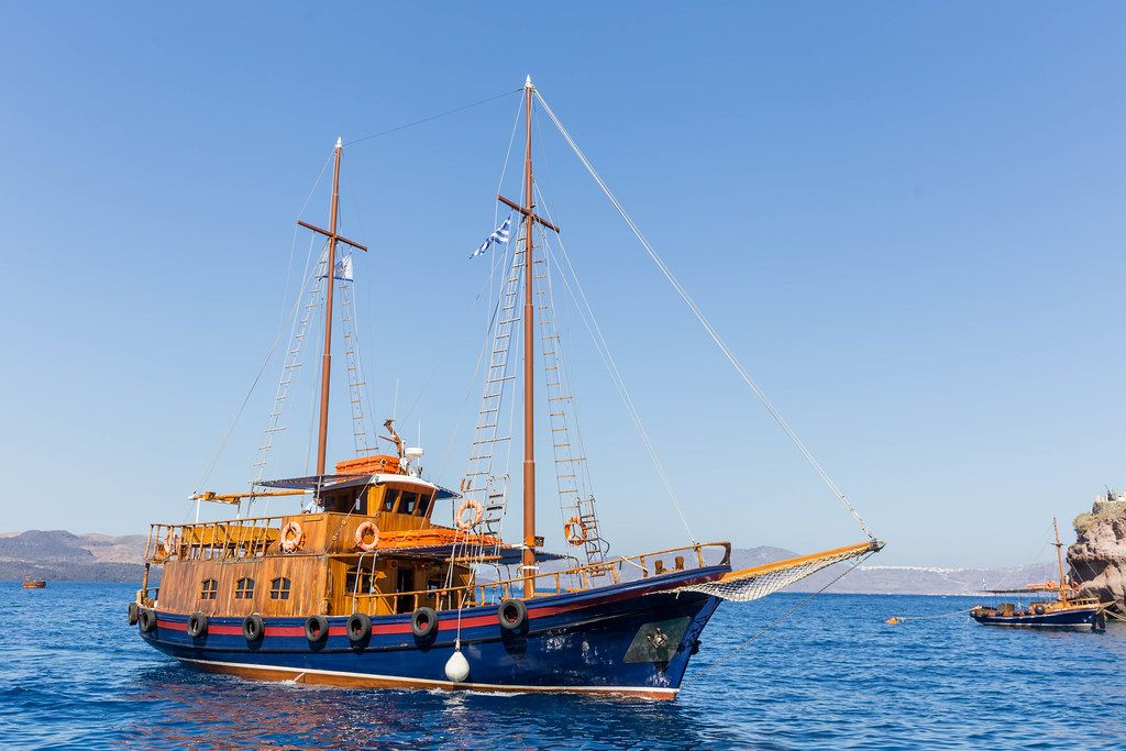 A sailboat with Greek flag by the coast in Santorini on a summer day