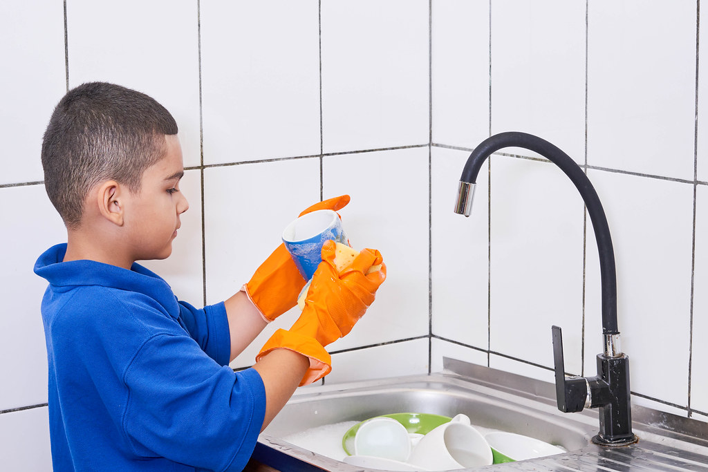 A schoolboy in blue shirt helping his mother with dishwashing