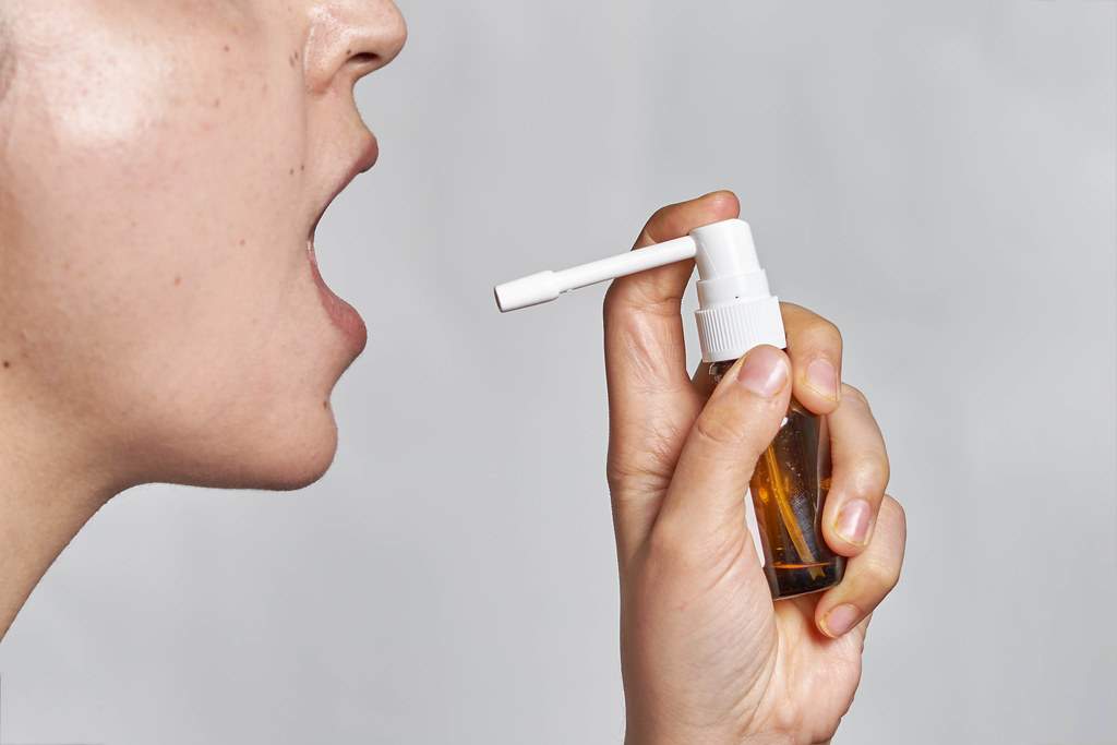 A sick woman using spray for throat