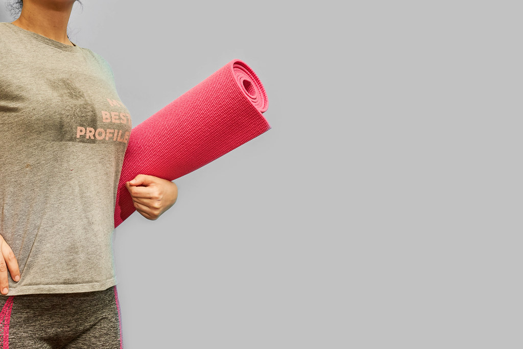 A slim lady with rolled yoga mat posing over grey background