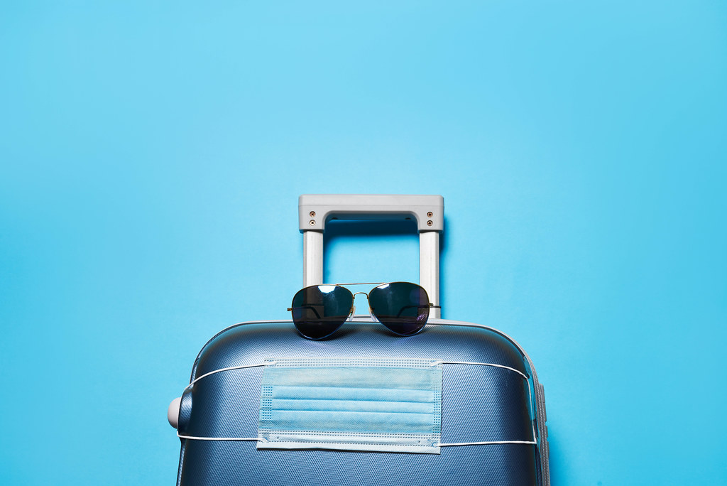 A suitcase with sunglasses and protective medical mask over blue background with copy space