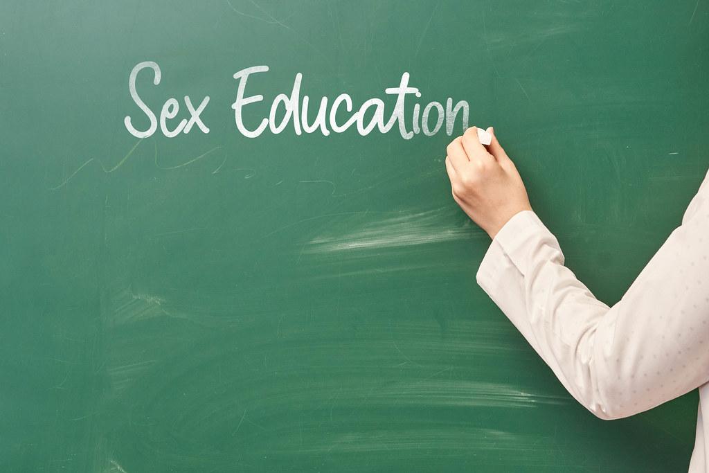 A teacher writing sex education on the chalkboard