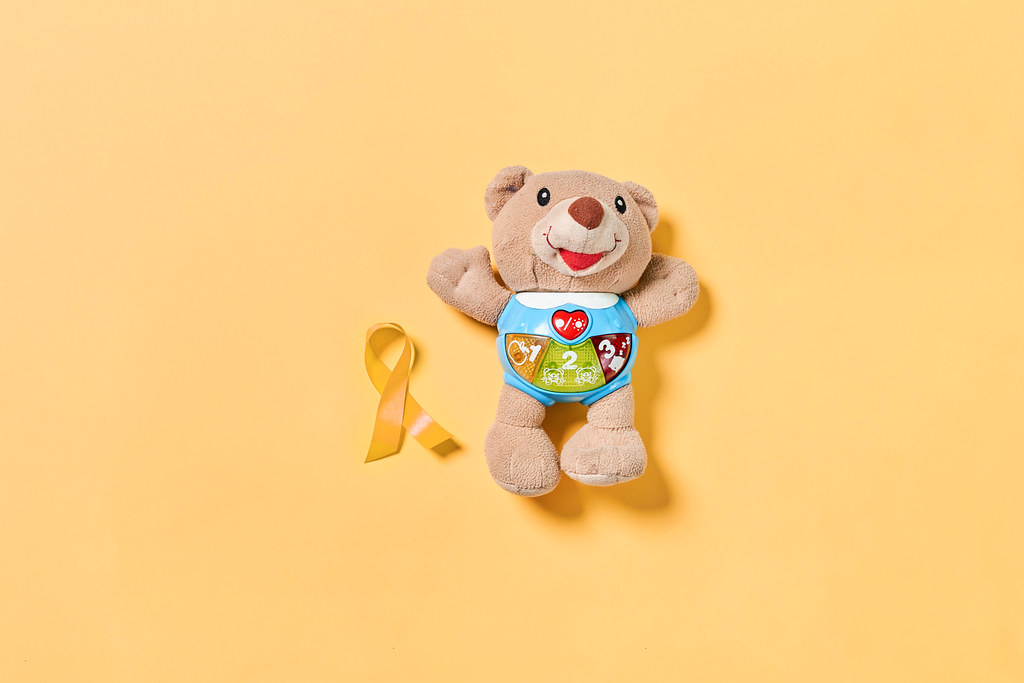 A teddy bear with childhood cancer awareness yellow ribbon. February, 15 - Childhood Cancer Day