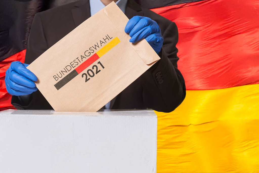 A voter putting a voting ballot into the election box over German flag