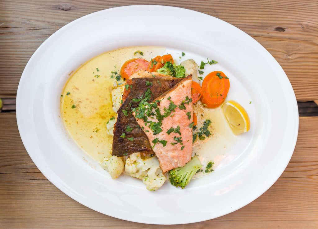 A white plate with char, cauliflower, broccoli, carrot and herbs. Typical fish from the Alpine lakes