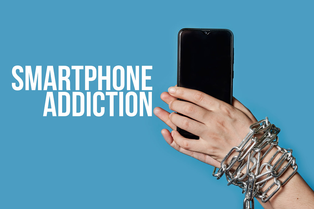A woman hand in chain holding a mobile phone, as a symbol of smartphone addiction