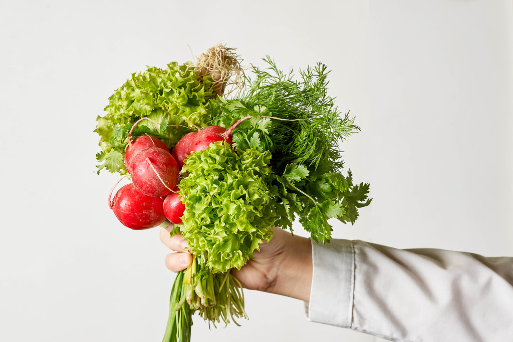 A woman holding a bunch of fresh radish and spring greenies