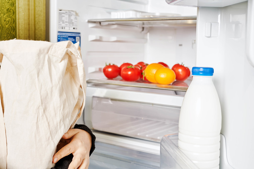 A woman holds a shopping bag full of foodstuff near the open fridge