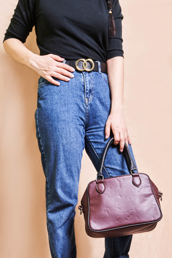 A woman in a trendy spring outfit with a leather handbag