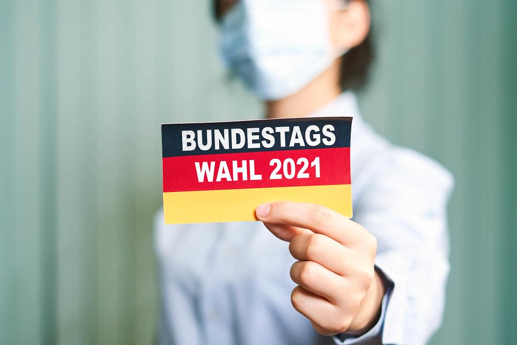 A woman in face mask holds German flag - Bundestagswahl 2021