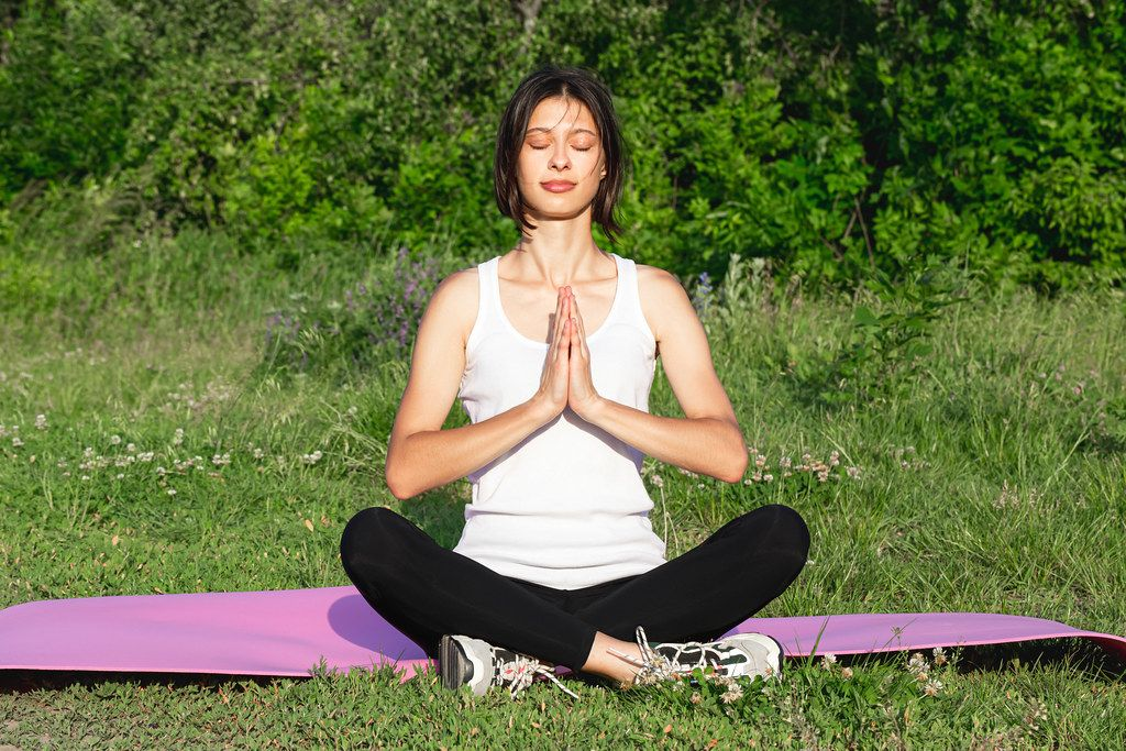 A woman in the Siddhasana position is engaged in meditation in nature