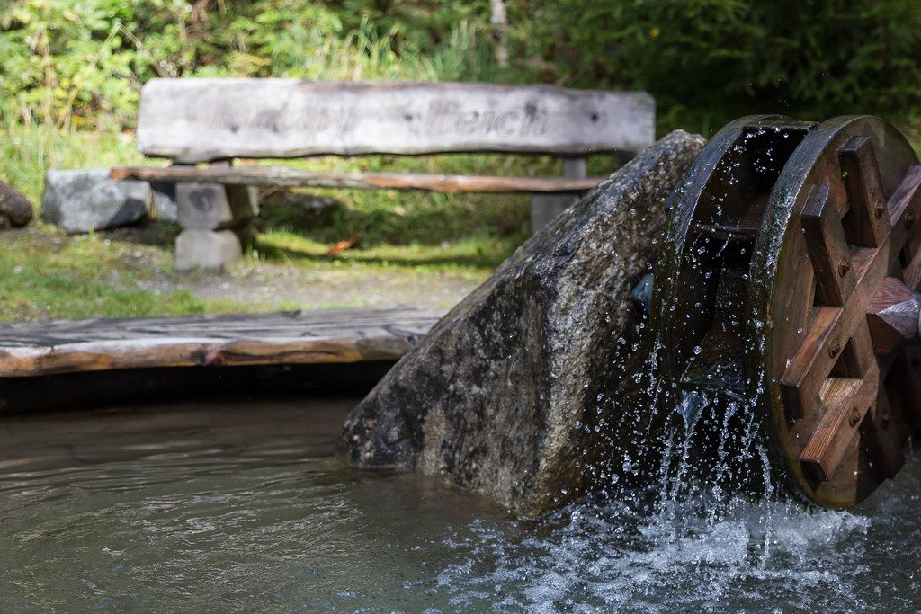 A wooden bench by the small pond with flowing water and mill wheel at the Mühlbach hike, Alpbach