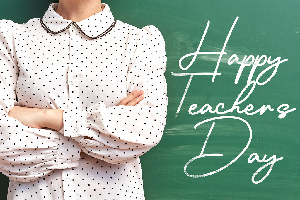 A young teacher posing over chalkboard - Happy teachers day concept