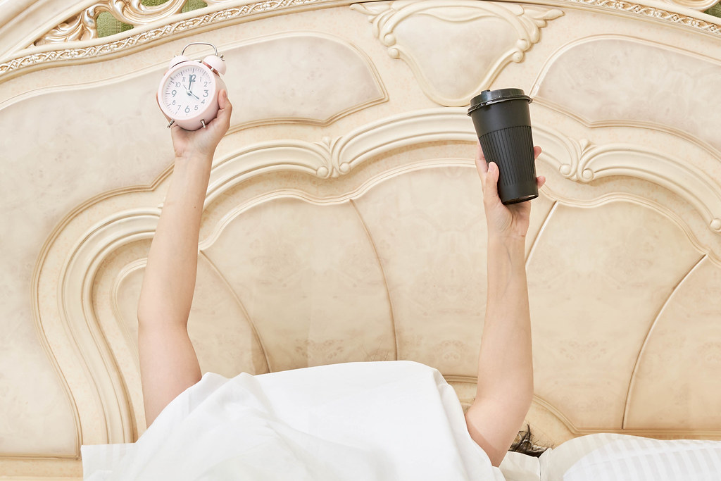 A young woman arms raised up holding a coffee cup and alarm clock in the bedroom