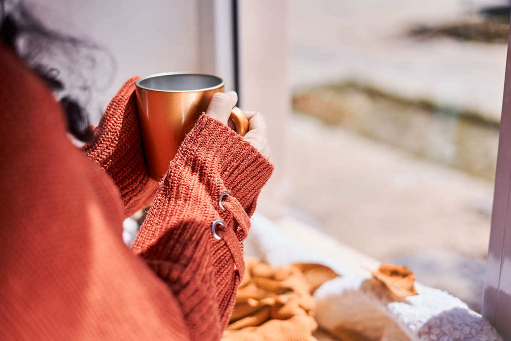 A young woman enjoying hot coffee and looking outside to autumn day near the windows