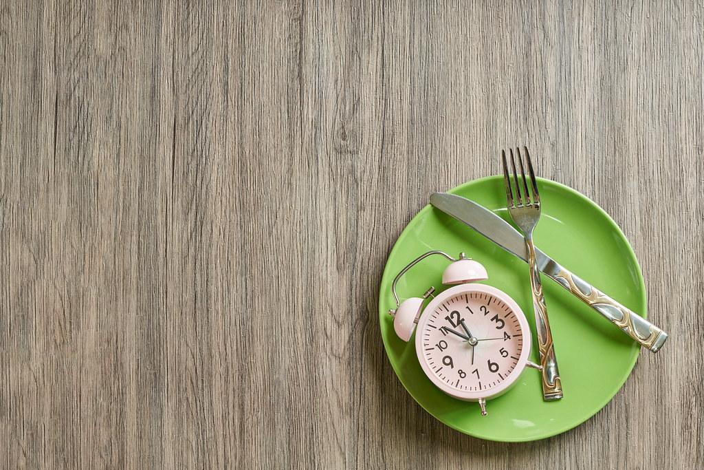 Ab in die Mittagspause! Geschirr und Wecker vor einem hölzernen Hintergrund. Aufnahme von oben