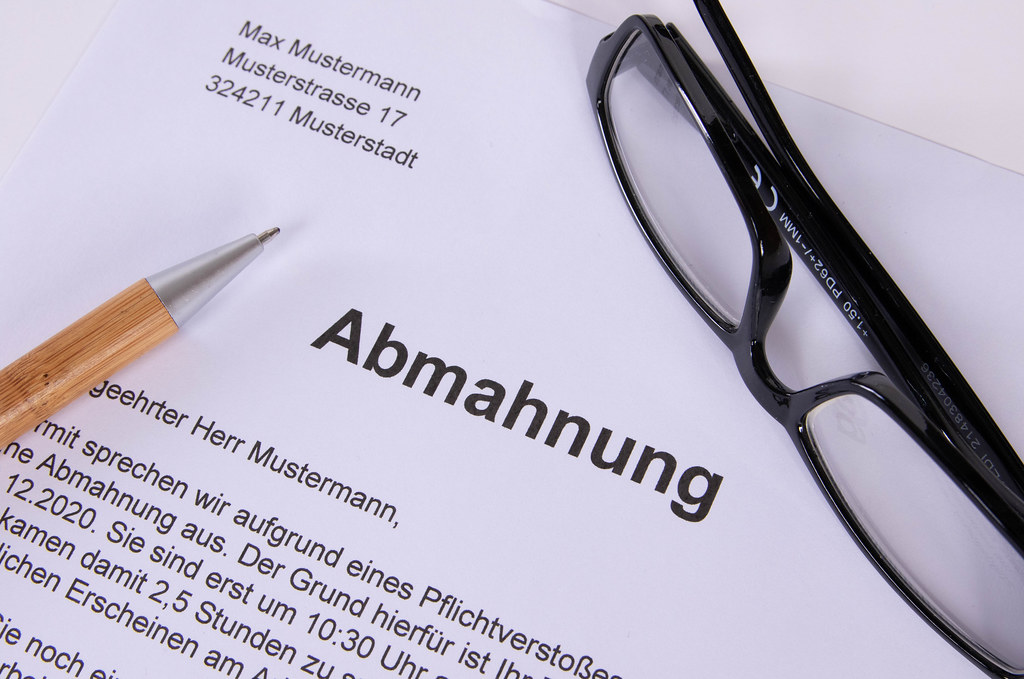 Abmahnung document with glasses and pen