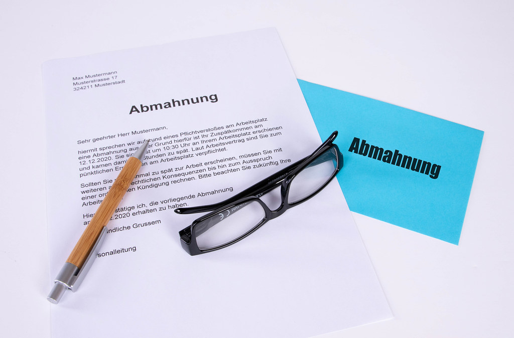 Abmahnung document with pen, glasses and blue envelope on white table