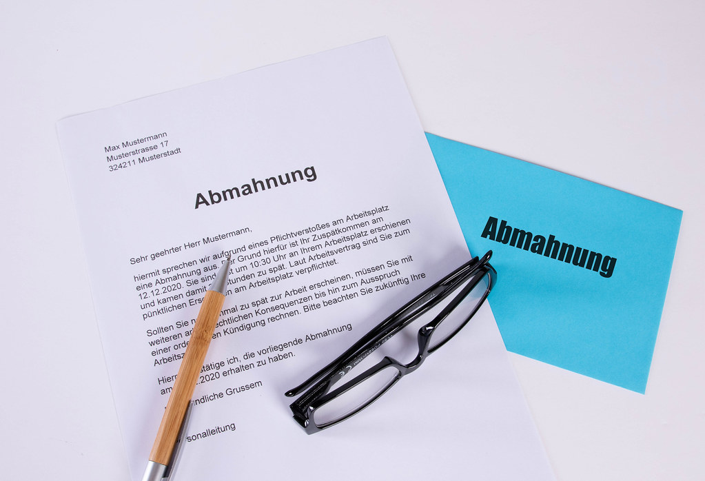 Abmahnung document with pen, glasses and envelope on white table