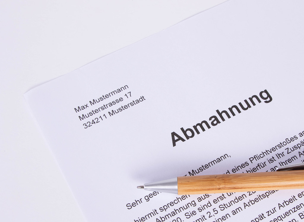 Abmahnung document with pen on white table