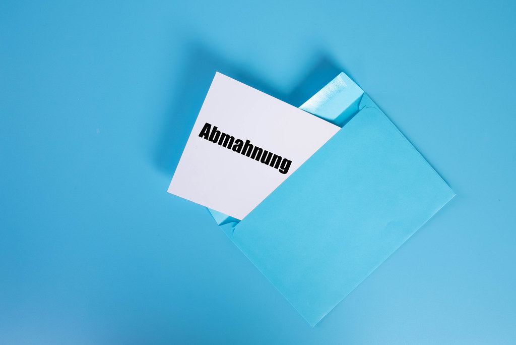 Abmahnung text with an envelope on blue background